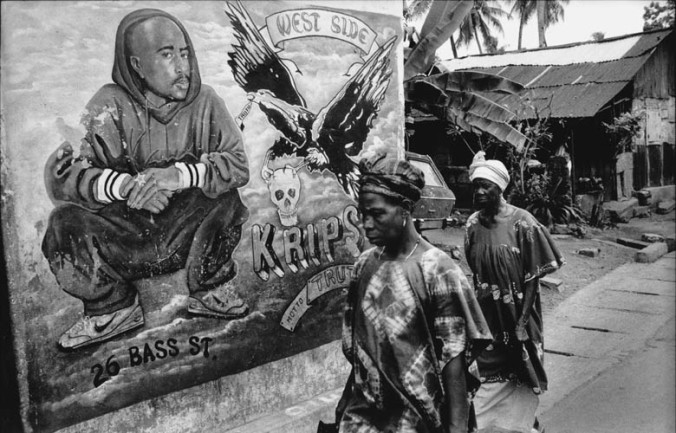© teun voeten Freetown, sierra leone, december 1999 women walking by mural of gangsta rapper tupac shakur. tupac was very popular with the rebels.